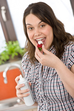 Photo Plus size woman with whipped cream on strawberry in kitchen