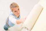 Fotografia Home improvement - handywoman painting wall