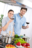 Smiling couple drink red wine cooking in kitchen