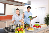 Young happy couple cook in kitchen with cookbook
