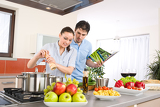 Fotografie Young happy couple cook in kitchen with cookbook