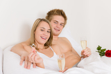 Engagement ring - couple in bed with champagne