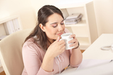 Happy businesswoman having coffee break at office