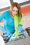 Fotografia Young woman cleaning stove in kitchen