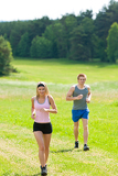 Sportive young couple jogging meadows sunny summer