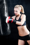 Boxing training woman in gym punching bag