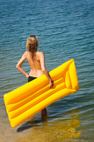 Summer woman hold yellow floating mat