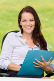 Fotografie Businesswoman in nature attractive smile folder