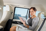 Fotografie Executive businesswoman in car work touch tablet