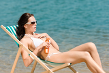 Fotografie Summer slim woman sunbathing in bikini deckchair