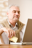 Senior mature man - home shopping with credit card