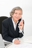 Fotografie Senior businesswoman smile sit behind office desk