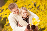 Fotografie Autumn happy couple holding leaves in  park