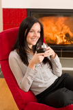 Fotografie Winter home fireplace woman glass red wine