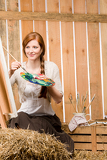 Fotografie Red-hair romantic woman painting in barn country