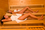 Sauna two women relaxing lying wrapped towel