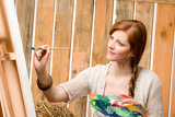 Fotografie Red-hair romantic woman in barn painting country