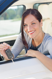 Attractive businesswoman in new car showing keys