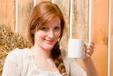 Fotografie Young romantic woman in barn holding cup
