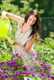 Photo Gardening smiling woman watering can violet flower