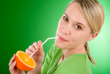 Healthy lifestyle - woman drink juice from orange