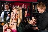 Fotografia Attractive girl at bar smiling with friends