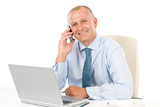Smiling businessman sitting in office behind desk