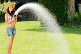 Fotografie Summer garden woman play with water hose