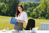 Fotografie Businesswoman in sunny nature office hold folders