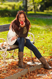 Autumn attractive woman eat apple sunset park