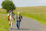 Hiking young couple backpack tramping asphalt road