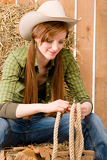 Fotografie Young cowgirl western country style with rope
