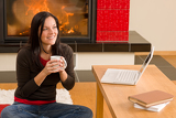 Home living woman with laptop by fireplace