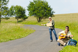 Hitch-hiking young couple backpack asphalt road