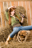 Fotografie Provocative young cowgirl drink beer in barn