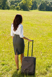 Fotografie Businesswoman sunny meadow leaving with luggage