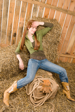Fotografie Provocative position young cowgirl on hay