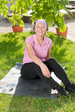 Senior sportive woman sitting on mat sunny
