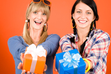Two young woman friends hold party presents