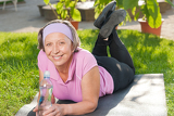 Fotografia Senior sportive woman lying on mat sunny