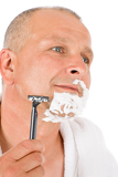 Fotografia Male cosmetics - Mature man shaving his beard