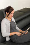 Businesswoman touch tablet computer leather sofa
