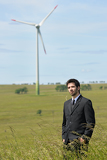 Green energy - Young businessman in field windmill