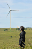 Fotografia Green energy - Young businessman point windmill