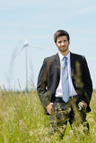 Fotografia Green energy - Young businessman in field windmill