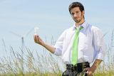 Fotografia Green energy businessman in field hold bulb