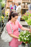 Garden centre woman hold white surfinia flower