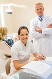 Dentist with assistant smiling at dental surgery