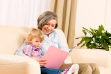 Fotografie Grandmother and granddaughter read book together