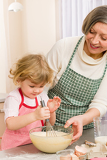 Grandmother and granddaughter whisk dough